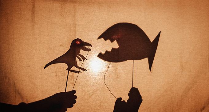 Två skuggspelsfigurer, en dinosaurie och en fisk.