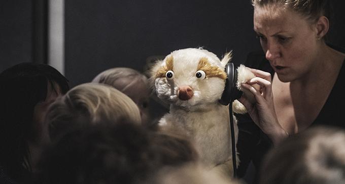 I förgrunden museets maskot, dockfiguren Scengångaren, som lyssnar på hörlurar. I bakgrunden museivärd och barn.